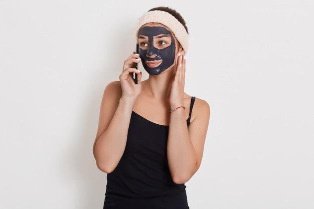 Blanke vrouw met haarband op hoofd en zwart gezichtsmasker praten met haar vriend met behulp van mobiele telefoon geïsoleerd over witte muur, opzij op zoek.