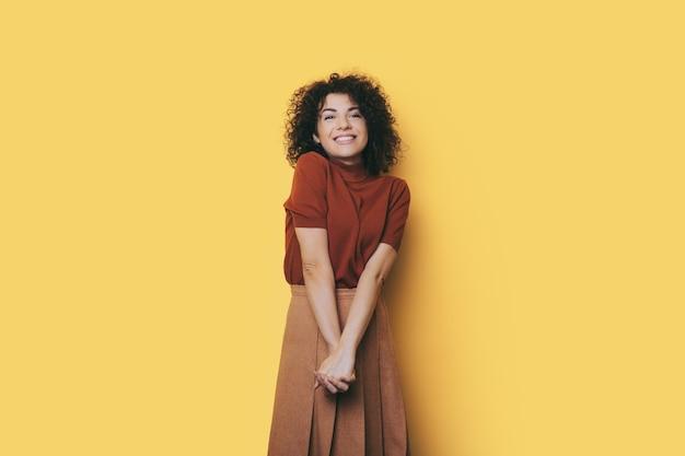 Blanke vrouw met krullend haar lacht naar de camera op een gele muur in een modieuze jurk