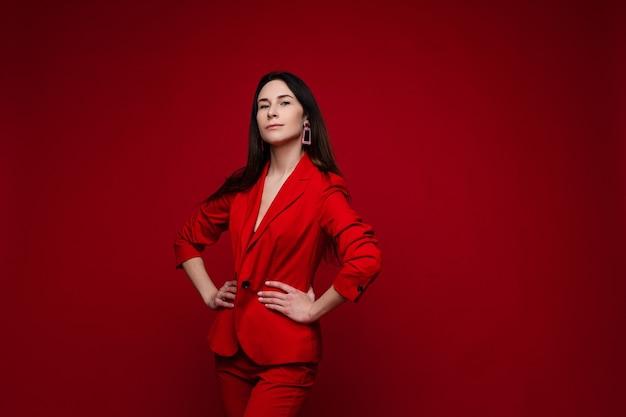 Blanke vrouw met lang donker steil haar in een rood kantoorpak, zwarte schoenen poseert voor de camera