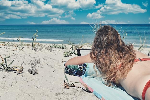 Blanke vrouw met lang haar, gekleed in een rode bikini, liggend op het strand naast de blauwe zee
