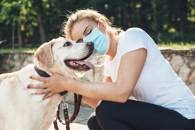 Blanke vrouw met medisch masker en blond haar omhelst haar labrador tijdens het wandelen in een park