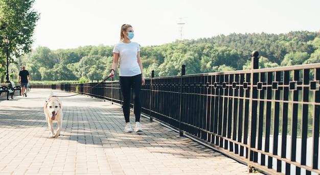 Blanke vrouw met medisch masker en haar hond wandelen in een park in de buurt van het meer op een zonnige zomerdag