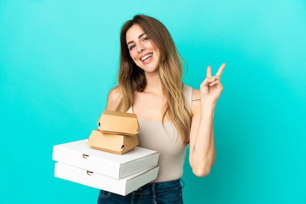 Blanke vrouw met pizza's en hamburger geïsoleerd op blauwe achtergrond glimlachend en overwinningsteken tonen
