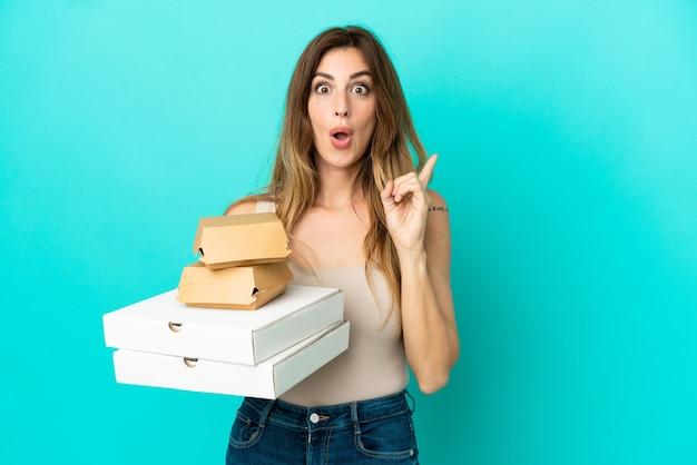 Blanke vrouw met pizza's en hamburger geïsoleerd op een blauwe achtergrond met de bedoeling de oplossing te realiseren terwijl ze een vinger opsteekt