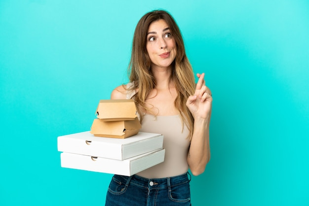 Blanke vrouw met pizza's en hamburger geïsoleerd op een blauwe achtergrond met vingers die elkaar kruisen en het beste wensen