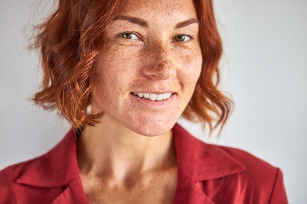 Blanke vrouw met rood haar en groene ogen poseren, glimlachend in de camera geïsoleerd in studio achtergrond, mensen en levensstijl concept