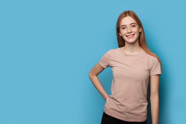 Blanke vrouw met sproeten en gemberhaar poseren op een blauwe muur glimlachend in de camera
