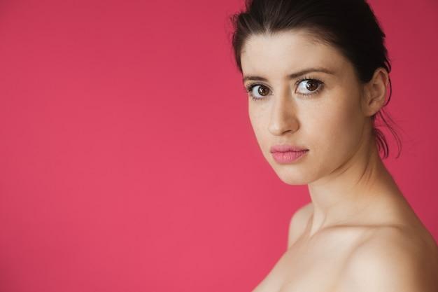 Blanke vrouw met sproeten en naakte schouders poseren op een roze achtergrond met vrije ruimte naar voren kijken