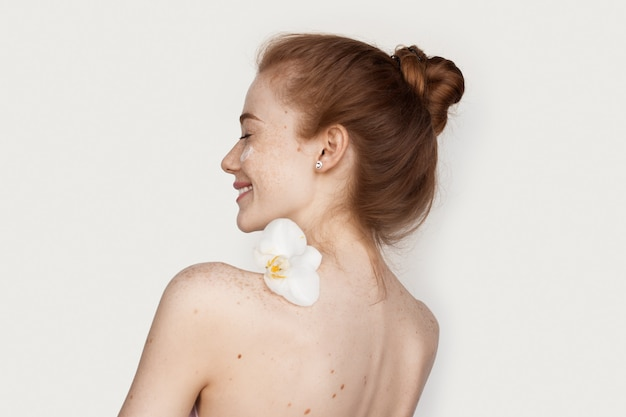 Blanke vrouw met sproeten en rood haar met een bloem op haar schouders lachend met een crème op gezicht op witte muur