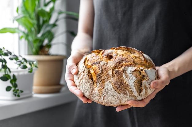 Blanke vrouw met vers brood uit de oven die zelfgebakken brood bakt