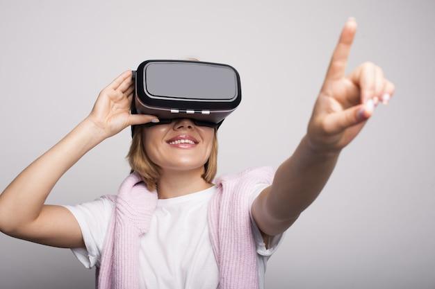 Blanke vrouw met virtual reality-ervaring met behulp van een hoofdtelefoon en iets op een grijze muur aan te raken