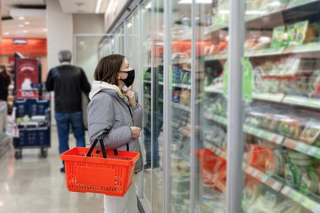Blanke vrouw met zwart gezichtsmasker met rood winkelmandje