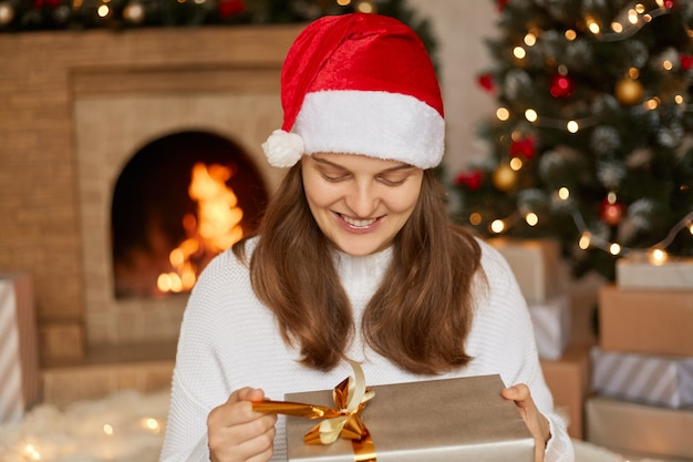 Blanke vrouw ontvangt verrassingsgeschenken op eerste kerstdag en opent de huidige doos