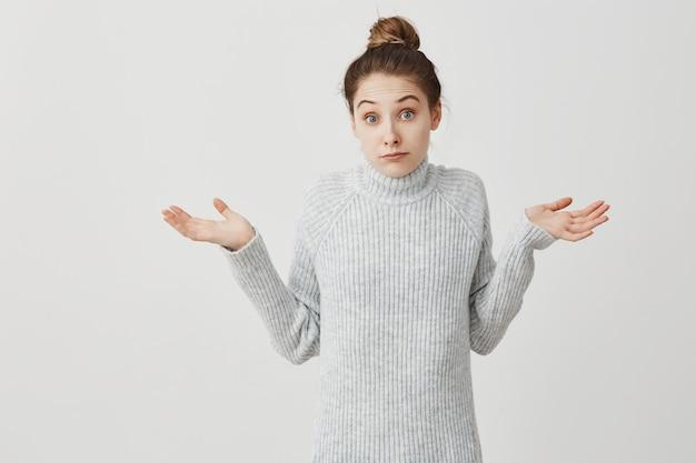 Blanke vrouw overgeven handen met onzekerheid op het gezicht. vrouwelijke startende ondernemer die zich gedraagt als heb geen idee of geeft niet om witte muur. emoties concept