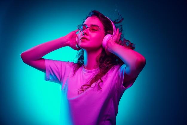 Blanke vrouw portret geïsoleerd op blauwe achtergrond in veelkleurige neonlicht.
