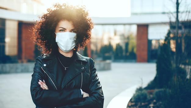 Blanke vrouw poseren met gekruiste handen terwijl het dragen van een anti-griepmasker en camera kijken