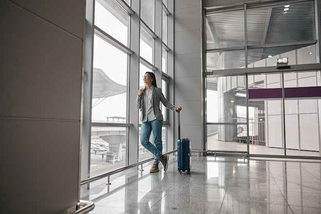 Blanke vrouw staat alleen in de buurt van panoramische ramen van de luchthaventerminal met bagage