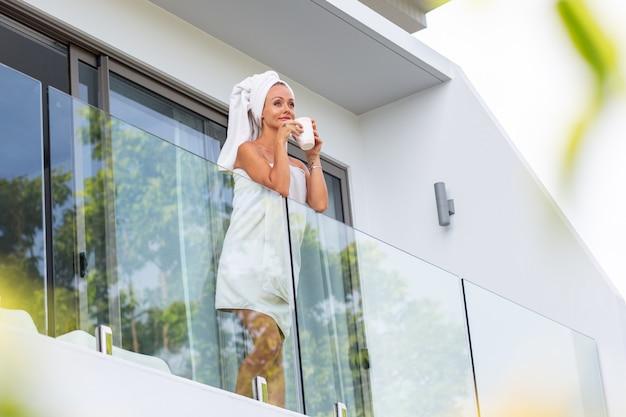 Blanke vrouw staat na het douchen in handdoek op het balkon van de villa en drinkt koffie of thee perfect begin van de dag rustig ontspannen vrouw ontmoet nieuwe dag