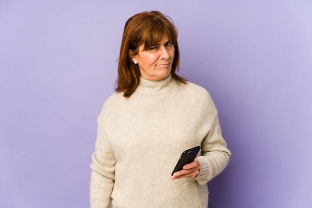 Blanke vrouw van middelbare leeftijd die een telefoon vasthoudt, is verward, voelt zich twijfelachtig en onzeker.