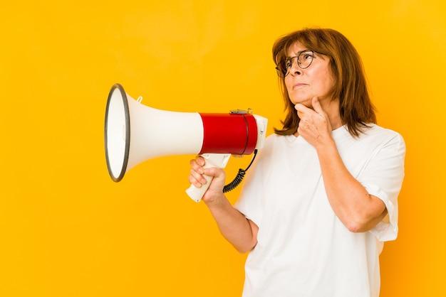Blanke vrouw van middelbare leeftijd met een megafoon die zijwaarts kijkt met een twijfelachtige en sceptische uitdrukking.