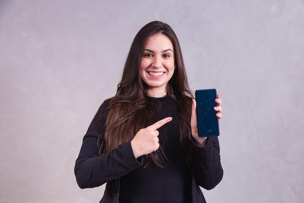 Blanke vrouw wijzend op mobiele telefoon met ruimte voor tekst op grijze achtergrond.
