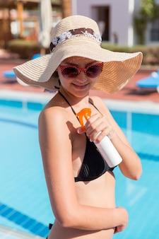 Blanke vrouw zet zonnecrème op haar schouder bij het zwembad onder de zon op een zomerdag. zonbeschermingsfactor in vakantie, concept.