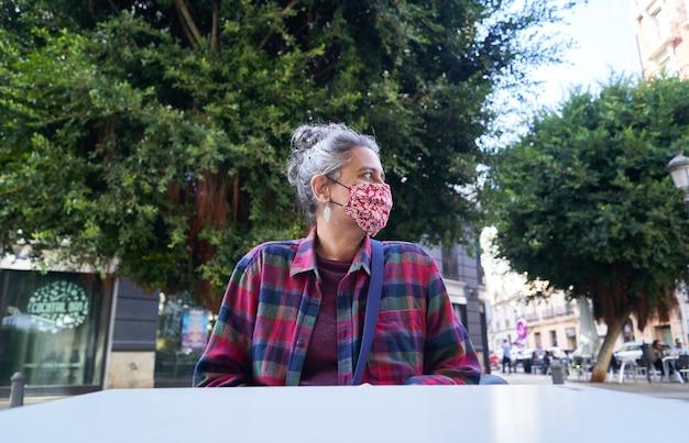 Blanke vrouw zit in een café met een medisch masker vanwege covid-19 - het nieuwe normale concept