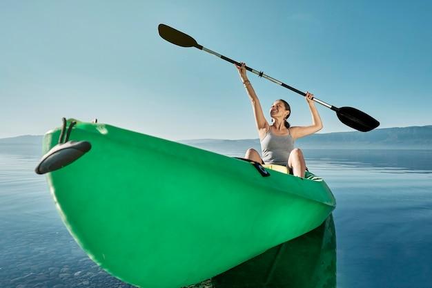 Blanke vrouw zittend in een groene kajak die de peddels naar de hemel opheft.