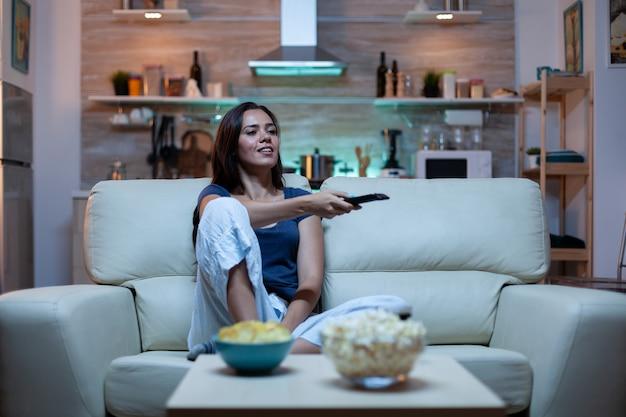 Blanke vrouw zittend op de bank en tv kijken ontspannen na het werk. opgewonden geamuseerde alleenstaande dame in pijamas rustend met snacks en sap zittend op een comfortabele bank in de open ruimte woonkamer.