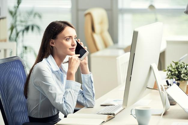 Blanke vrouwelijke beambte zit aan bureau voor scherm en praten op smartphone