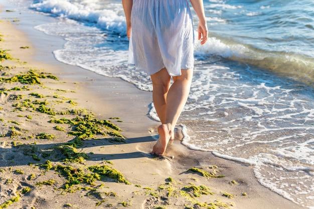 Blanke vrouwelijke voeten lopen op het zand van het strand in de buurt van de zee of de oceaan bij zonnig zomerweer. reis reizen concept