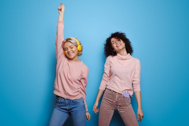 Blanke vrouwen luisteren naar muziek en dansen op een blauwe muur met koptelefoon