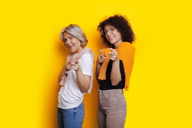 Blanke vrouwen met krullend haar wijzen vrolijk naar de camera terwijl ze poseren op een gele vrije ruimte achtergrond