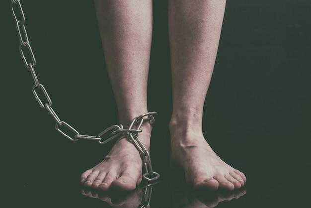 Blanke vrouwen voeten zijn op de vloer geketend metalen kettingen close-up