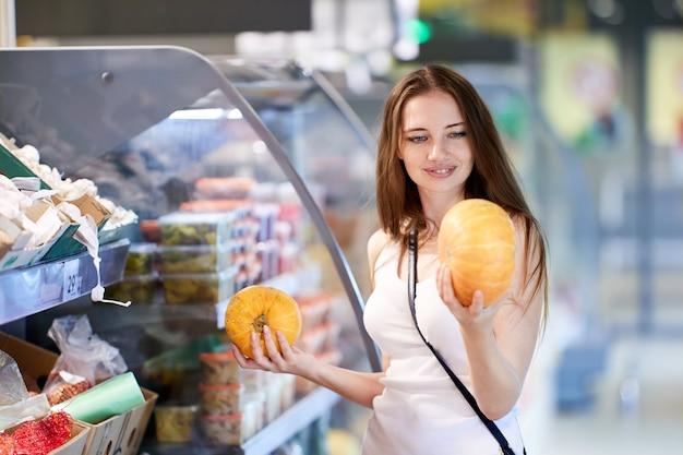 Blanke vrouwenkoper kiest pompoen in supermarkt voor halloween
