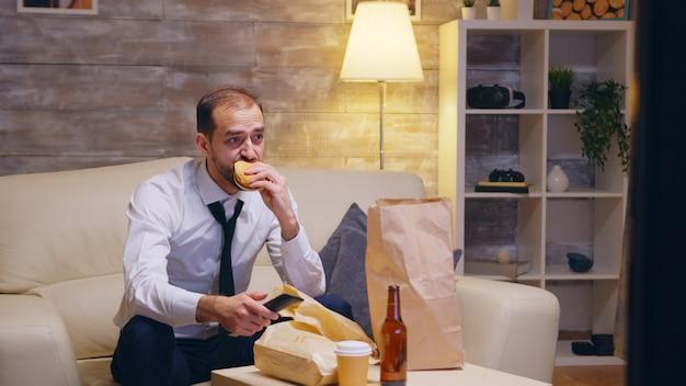 Blanke zakenman die zijn stropdas losmaakt terwijl hij op de bank zit na een lange dag op het werk. hamburger eten.