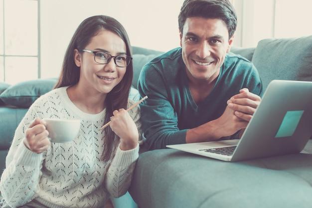 Blanke zakenman en aziatische zakenvrouw dragen casual kleding die samen in de woonkamer zit en op een laptop-notebookcomputer werkt met ontspanning en geluk. idee voor modern thuiswerken