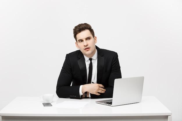 Blanke zakenman zit aan een bureau en kijkt en denkt op kantoor