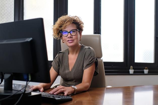 Blanke zakenvrouw die lacht met een bril die in een bureau zit met een computer die naar de camera kijkt.