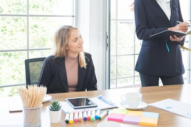 Blanke zakenvrouw zitten en kijken in vergaderruimte conferentieruimte met multi-etnische medewerker.
