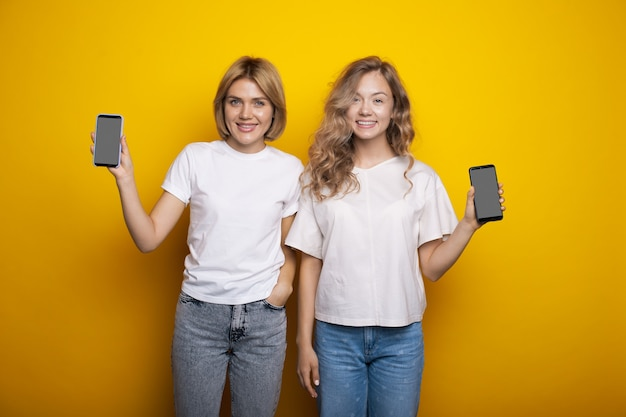 Blanke zussen adverteren iets op hun telefoon met het scherm en glimlachen op een gele muur