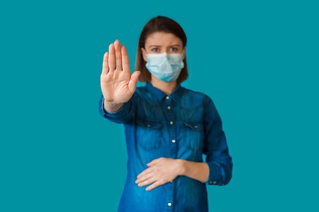 Blanke zwangere vrouw gebaren stopbord op een blauwe achtergrond terwijl het dragen van een speciaal masker
