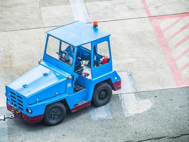 Blauw bagage slepend voertuig op de luchthaven