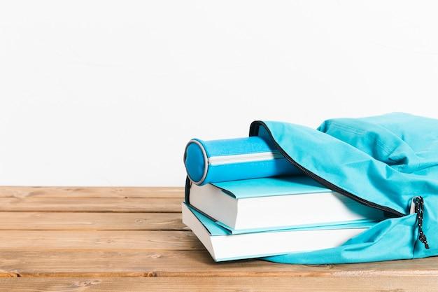 Blauw boeken en potlodengeval in het openen van schooltas op houten lijst