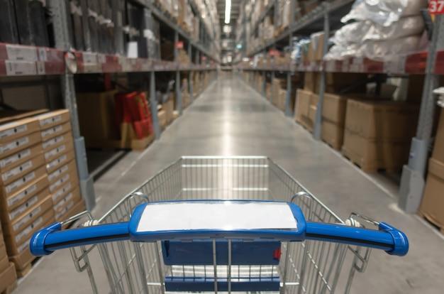 Blauw boodschappenwagentje met vage mening van pakhuisbinnenland met product op planken op het centrumachtergrond van het warenhuiswinkelcomplex
