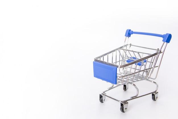 Blauw boodschappenwagentje of lege die supermarktkar op witte achtergrond met exemplaarruimte wordt geïsoleerd