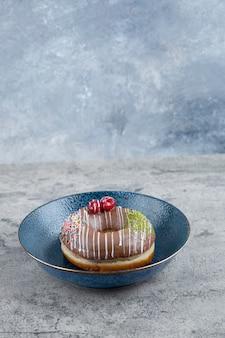 Blauw bord met chocolade donut met bessen en hagelslag op marmeren oppervlak.