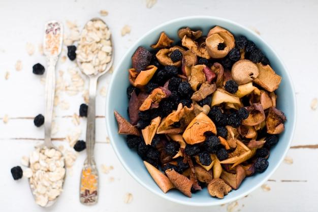 Blauw bord met gedroogde appels en bessen en een lepel havermout op een witte houten gezonde voeding.