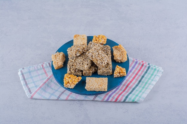 Blauw bord van snoepjes met verschillende noten en zaden op steen.