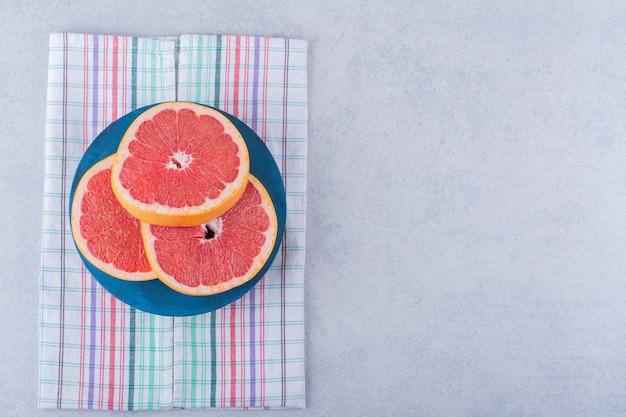 Blauw bord van verse grapefruit plakjes op stenen tafel.